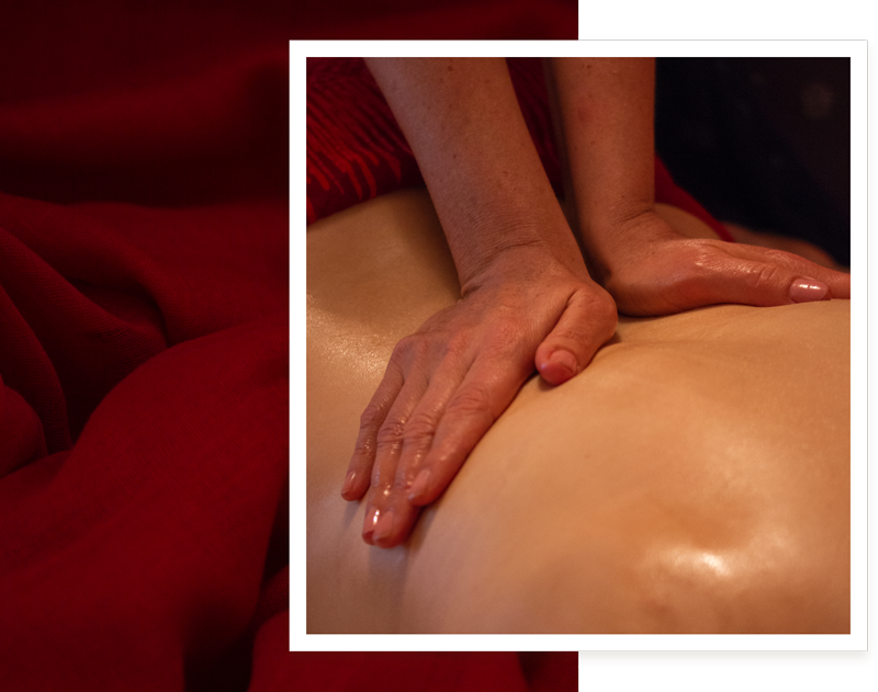 Close up of two hands on female back massaging oil into the glistening skin