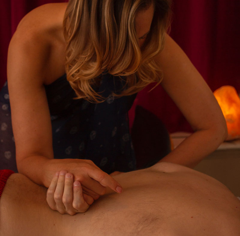 Massage therapist with hair across face bending over the back of a male client